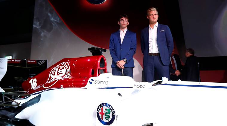 Drivers Leclerc and Ericcson pose next to the Alfa Romeo Sauber F1 car during a presentation in Arese
